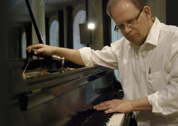 Portrait d'Allan Sutton accordant un piano
